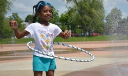 young girl with braids hula hooping at mlk park water fountains behind her