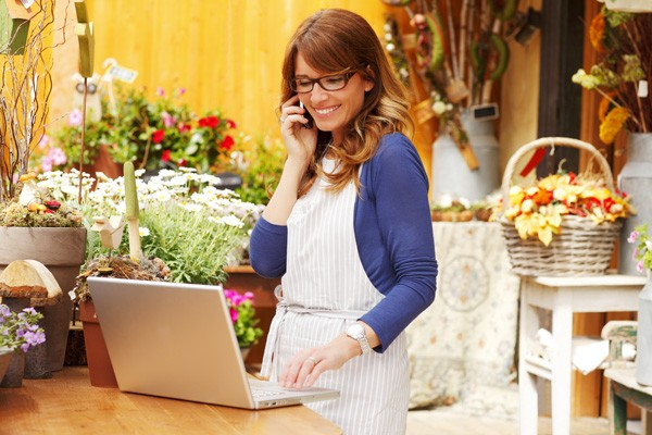 A woman, evidently a small business owner, smiling into phone while looking at laptop