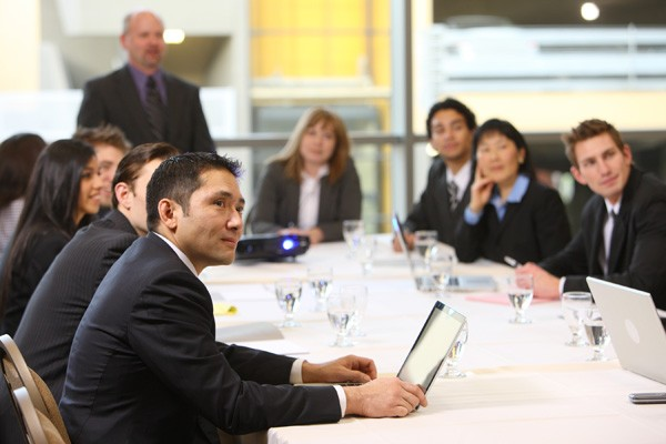 A large group of suited corporate professionals in conference room