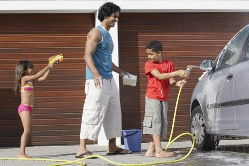 Boy helps father wash car while sister squirts them with squirt gun