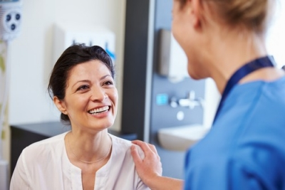 Patient smiles back at reassuring nurse