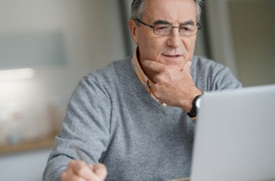 Man reads about different health care topics on laptop