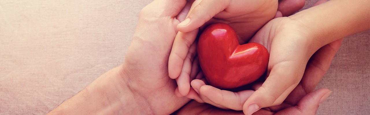 two people holding a heart in their hands