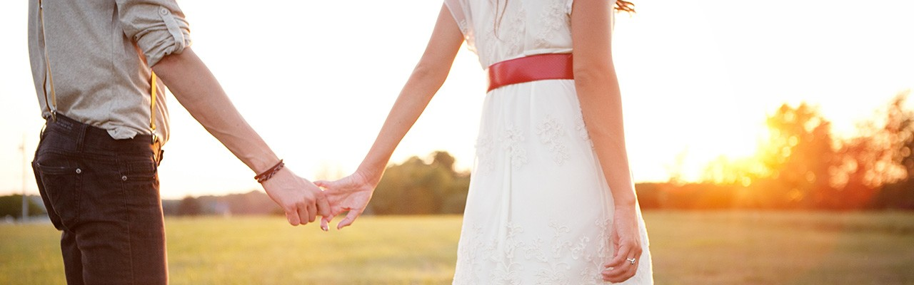 fertility-treatment-couple-holding-hands-in-field