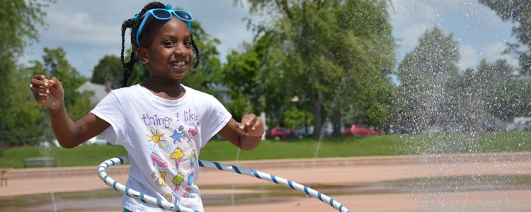 young girl with braids hula hooping at mlk park fountains behind her