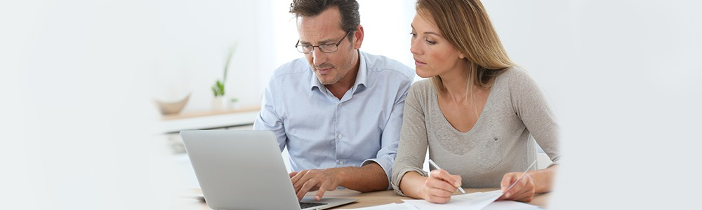 man and woman reading from a computer about healthcare fraud